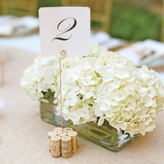 White hydrangeas in rectangular glass boxes made for a refined low centerpiece, while table names were held up with golden rods and placed i...