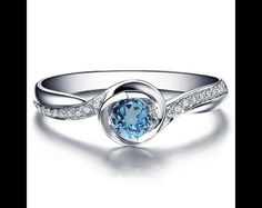 A beautiful round cut blue topaz engagement ring that is very comfortable to be worn daily and was designed with a lot of thought and love. This would be the perfect ring for proposal or a gift for...
