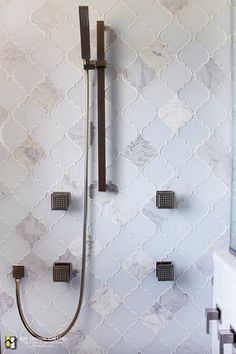 Body sprays and an adjustable/handheld shower head add to the luxury of this master shower. Glass and marble arabesque tile make for a stunning statement wall.