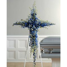 Beautiful floral cross funeral arrangement made using blue delphinium. Perfect for his funeral or memorial service.