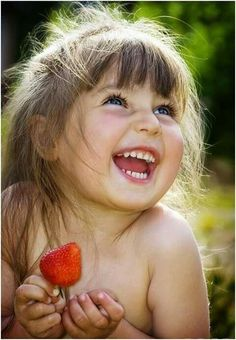 a kid laughing, having fun w/ strawberries