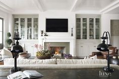 Inspired by Napa Valley, architect Eric Olsen gave a family's Newport Beach home a modern farmhouse style. William's Wood Works fabricated the tongue-and-groove ceiling in the living room, where glass-front cabinets flank a fireplace. The coffee table Style At Home, Living Room Designs, Home Living Room, Hamptons Living Room, Living Room Wall Units, Hamptons House, Kitchen Living, Living Area, Fireplace Built Ins