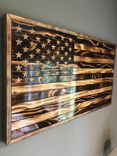 This American flag is made from pine and is burned to bring out the unique grain in each piece. The stars are hand engraved and slightly charred to add a rustic look. The dimensions are 37.5x 19.5x 1.5 and it weighs approximately 10 pounds. Each flag has 3 coats of polyurethane
