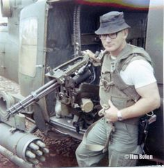 Jim standing next to a Huey gunship's mini gun and fully loaded rocket pods, before he went on a separate mission - as a door gunner, which we talk about in a later interview.