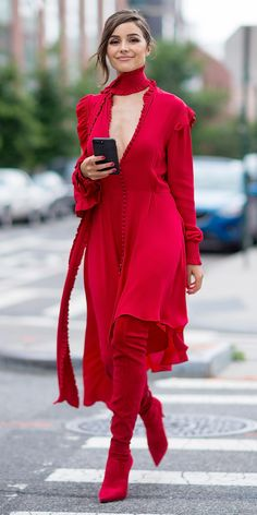 Olivia Culpo channeled her inner dancing lady emoji while out in Long Island City, wearing a killer all red everything ensemble: a plunging Magda Butrym dress with asymmetrical sleeves, a matching scarf, and thigh-high pointed toe boots. S