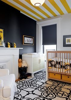 Fun black, white and yellow nursery with black accent wall and a white and yellow striped ceiling! The nursery features a traditional white fireplace topped ...