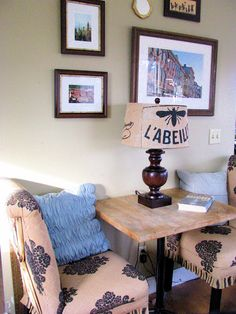 Facing chairs and a table make a comfy nook. Pillows against wall warm it up. Nice for tea, cards, board games, reading or just a chat. Would also work with wall or ceiling mounted lighting.