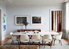The dining room adjoins the open living area and is grounded by the cool-toned Ashra rug by Ben Soleimani for Restoration Hardware. Midcentury-style Saarinen for Knoll dining chairs and a marble-topped Poliform table complete the scene.