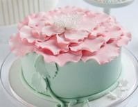 Mini cake in soft green topped with large pink flower