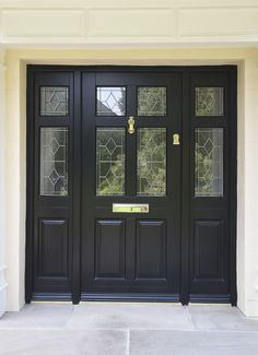 Frenchay style entrance door with sidelights, finished in Black. Queen Anne decorative glazing on Kathedral obscure glass. Brass Doctor's knocker and letter plate. Manufactured in Engineered Meranti Hardwood. Timber Front Door, Hardwood Front Doors, Composite Front Door, Black Front Doors, Double Front Doors, Front Door Entrance, House Front Door, House Entrance, Front Door Paint Colors
