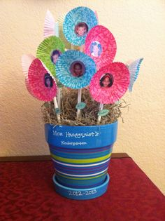 This was my son's teacher appreciation gift for his Kindergarten teacher.  I used their class picture and punched out 1 inch sized faces.  We glued them onto mini muffin cupcake liners and glued them to cake pop sticks.  We filled the flower pot with foam and used spanish moss to cover it up.  We also added leaves to the flowers with the kids names on them.  To finish it off we used a paint marker to add the teacher's name and school year.  My son signed the bottom of the flower pot.