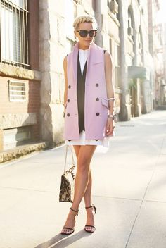 Blair Eadie wears a white mini shirtdress and layers with black and pink vests. She accessorizes with a leopard bag and thin black sandals