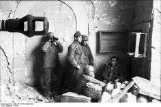 Inside the first large opening (of five total openings) opening from the south of the Palazzo Iucci. This area was where the Sturmgeschütz from Stug.-Brigade 242 was stationed between strikes against the allies. Identified soldiers: seated without cap is Hauptmann Rudolf Rennecke, Kommandeur II./Fallschirmjäger-Regiment 3; standing, wearing field cap is Feldwebel Eugen Opel, Kommandeur of the Stug III.