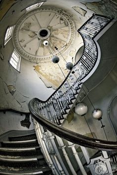 Modern ball chandelier in the impressive stairwell of an abandoned mansion.