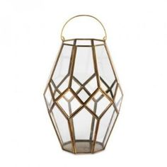 Large Brass Mohani Lantern : These stunning Mohani brass lanterns have a bold geometric design that is enhanced by the striking brass finish. The elegant contrast of silver and glass combines perfectly with the bold design.