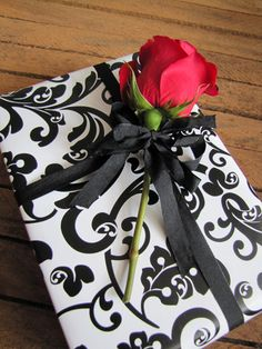 Elegant Gift Wrap, using black & white wrapping paper, adding a long stem rose! Silk flowers can be purchased on sale and used to dress up packages for all occasions, very pretty and definitely stands out more than a bow!! #giftwrapping #flowers #emballagecadeau