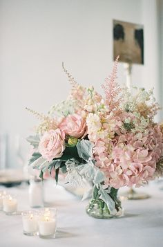 Centerpieces: pedestal mercury vase, pink astilbe, feather plume, blush stock, hydrangea, dusty miller, milky way roses, garden roses.