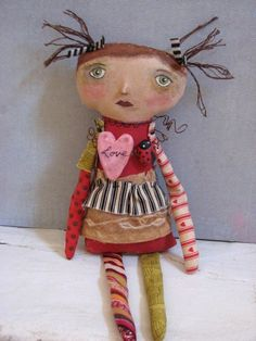 Sewn from muslin, painted and stained for a primitive time-worn patina. This little Valentine Doll measures about 12 tall. Her arms and legs are sewn from assorted fabrics. Her hair is painted with floss. Hand painted facial features with a clay nose. Hanging from her neck is a hand