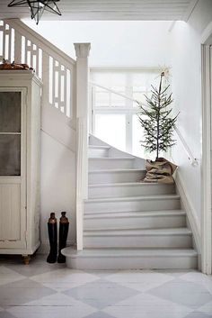 This tree on the stairs is so lovely:  it's Charlie Brown style, burlap base, and crowning star. Just charming.