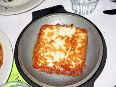 Saganaki is a Greek or Greek-American dish consisting of a hard, white, brined cheese cooked simply with olive oil in a hot pan (traditionally a two-handed vessel whence the name of the dish), usually served with lemon. European Cuisine, Eastern Cuisine, Flaming Cheese Recipe, Saganaki Recipe, Greek Appetizers, Greek Desserts, Cheese Fries, Fried Cheese, American Dishes