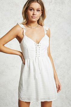 A textured woven dress featuring a V-neckline, sleeveless cut with flounced adjustable straps, front lace-up with self-tie straps and high-polish grommets, an allover metallic striped pattern, a concealed side seam zipper, and an interior lining.