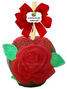 Manzana envuelta de caramelo con capa de chocolate semiamargo, decorada con flor de chocolate color rojo, hojas de fondant y perlitas de azúcar.