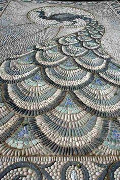 Unique Kieselsteine bilden ein Pfau Bild im Garten