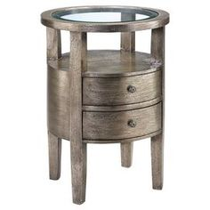 """Two-drawer end table with a beveled glass top and open shelf. Finished in metallic pewter over silver leaf. Product: End table        Construction Material: MDF, Asian hardwoods and glass Color: Silver Features: Two drawers with open shelf area    Beveled clear glass lay in top  Hand-painted textured metallic finish over silver leafing  Dimensions: 26"""" H x 18"""" Diameter"""