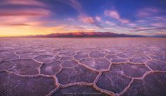 Being a small spec on a massive salt playa with mountains on both ends of me. The sun started to creep over the horizon behind me lighting up the mountains miles away from me. This is a 180 degree panoramic view of the salt flats at sunrise. I used nine vertical frames which were then stitched together for the final panorama. One of the classic scenes of death valley, and one of the most beautiful for sure. It's amazing how quiet it can get in some of these places out there.