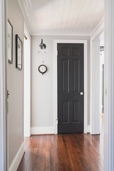 Hallway in a sophisticated palette of light gray and black, with beadboard ceilings, black trim and stoneware