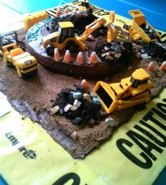 """Construction cake I made for my son's birthday party by Elizabeth Nehemias Cut cardboard box & lined it w/ wax paper & caution tape. Baked cake in 9"""" round pan. Excavated small hole from top & put it on the other side of cake. Transferred cake to job site. Iced it. Ground = brown sugar, cocoa powder, butter cream icing, & Demerara sugar. Food processed cookie part of Oreos for dirt piles. Placed CAT machines (5 pack $6 @ Target). Topped w/ chocolate candy rocks & candy corn construction…"""