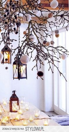 pom poms and lanterns hanging from branches make a magical holiday chandelier