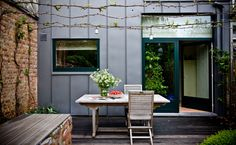 grapevines are trained up stainless steel cables to form a pergola.  The same cables are a framework for holding pendants above the table.