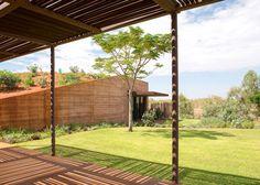 Luigi Rosselli builds housing behind a long rammed-earth wall