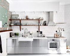PHOTO: Anders Bergstedt for Entrance This professional-looking stainless steel kitchen is actually a combination of IKEA cabinets and stainless steel cover panels. Utilize brass hardware on stainless steel cabinets for a modern take on industrial design.