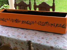Flower bed painted with orange latex and decorated with stencil of flowers, manually painted. //Maceta pintada con latex naranja y stencil de guarda de flores pintadas manualmente.