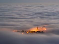 Asiago Plateau, Italy.   A town shrouded in fog as seen from the top of a mountain.
