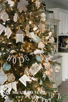 Miss Mustard Seed's Christmas tree: sheet music banner, paper rosettes, word silhouettes + lots of German glass glitter