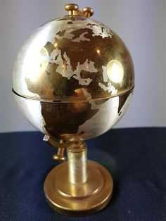 This is a lovely original vintage world globe cigarette holder / stand from the 1950s. It is made of gold and silver metal and measures 7 inches or 18 cm tall when closed and extends up to 12 inches or 30 cm when opened. It is in good condition for its age.