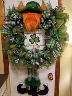 """Leprechaun St Patrick's Wreath is a fun way to show you're Irish and sure to bring a smile to anyone's face with his red beard, pointed ears, Shamrock hat, green pants and black boots. He is well made with lots of detail and hiding behind a """"Kiss Me I'm Irish"""" wood sign. The wreath is made of high quality green mesh with colorful ribbons, sparkly shamrocks, and other enhancements.  This is a large wreath, measuring roughly 20 inches across and 40 inches from head to feet."""
