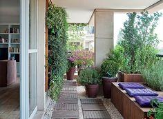 A varanda com jeito de quintal é exatamente o que a moradora deste apartamento queria. O paisagista Roberto Riscala escolheu o pínus de reflorestamento para a estrutura das caixas e do jardim vertical, que recebeu peperômias, columeias e samambaias (Foto: Célia Weiss/Casa e Jardim)