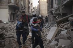 Youths carry children through a site damaged from what activists said was shelling by forces loyal to Syria's President Bashar al-Assad in the town of Douma, eastern Ghouta in Damascus, Syria December 30, 2015. REUTERS/Bassam Khabieh