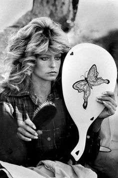 Farrah Fawcett brushes her famous feathered mane on the set of Charlie's Angels,1976~♛