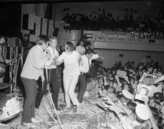 Normie Rowe performing on stage in front of a crowd at the Melbourne Town Hall on 18 December 1968. A teenage girl has rushed onto the stage in an attempt to approach the singer. At the time, Rowe was one of Australia's biggest pop stars