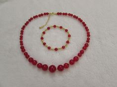 Necklace and bracelet set made with red dyed quartz with gold plated beads.