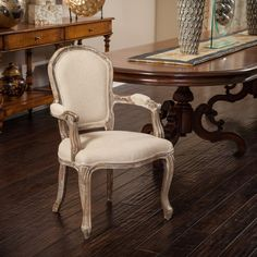 An exquisite piece down to the smallest detail, this elegant chair is the epitome of classic French style and design. The carved oak frame is distressed for a weathered look, while the well-padded seat and backrest are covered in versatile beige cotton.