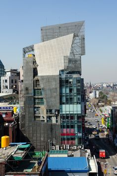 Sun Tower 37-38 Daehyeon-dong, Seodaemun-gu Thom Mayne/Morphosis, 1997  The Sun Tower, designed by Thom Mayne of Morphosis from Los Angeles, stands on two neighboring properties. The two property owners were in dispute. The building is severed vertically down the center to express this duality. From the street, the building appears to be two slender towers with a second skin attached. Photo: Martin Eberle