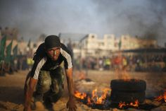 """A Palestinian boy crawls next to burning tyres during a military-style graduation ceremony at Fajer Al-Entesar (dawn of victory) summer camp, organized by the Hamas movement, in Gaza City June 19, 2014. Hamas stages dozens of military-style summer camps for young Palestinians in the Gaza Strip to prepare them to """"confront any possible Israeli attack"""", organisers said."""