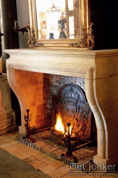 Limestone fireplace...LOVE the fireback!