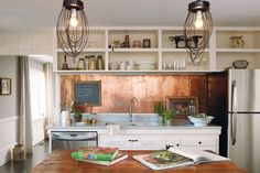 Cozy, light-filled space with open shelving, a copper backsplash, and stainless appliances